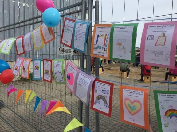 Am Zaun befestigte Wunschzettel der Schüler