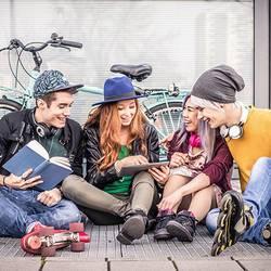 Jugendliche schauen sich auf dem Tablet was an.