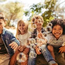glückliche Kinder spielen mit Seifenblasen